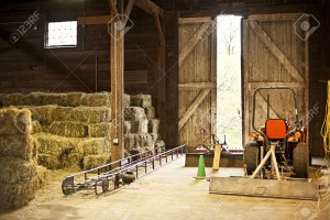 14384517-Interior-of-wooden-barn-with-hay-bales-stacks-and-farm-equipment-Stock-Photo